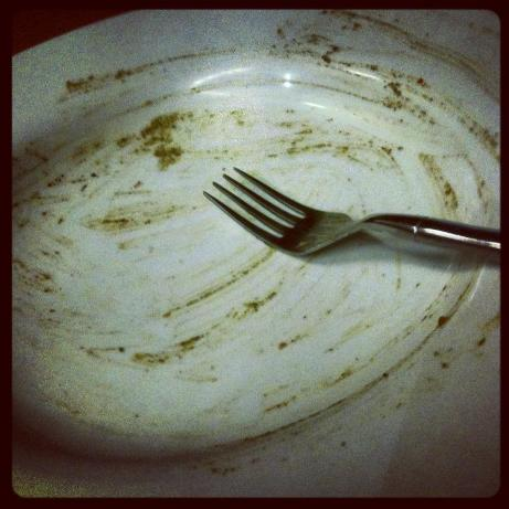 Empty plate and fork, smeared with spinach
